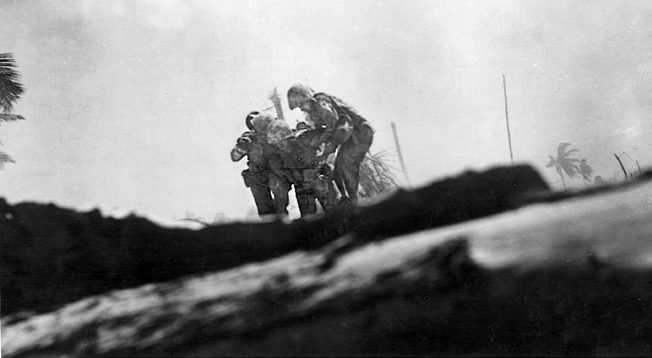 Two Marines help a wounded buddy to a place of safety during the fierce fighting on Tarawa. Nearly 1,000 Marines were killed in the three-day battle and over 2,000 were wounded. The enemy force fared far worse.