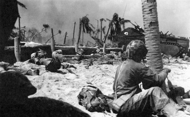 U.S. Marines, taking cover behind the low sea wall on Tarawa, watch as an amtrac advances toward an enemy position.