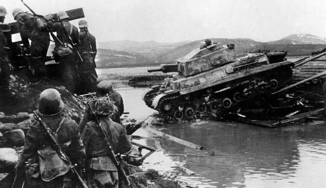 Hungarian panzergrenadiers accompany a Turan II across a stream in Russia in 1944.
