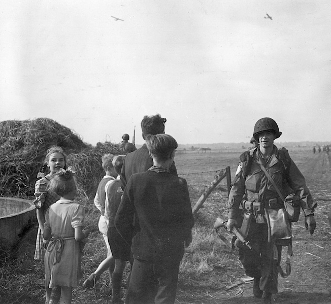 Although Operation Market-Garden ended in a bloody repulse, the initial air drop was executed with precision in daylight on September 18, 1944. Here, 101st Air- borne troops already on the ground move past Dutch civilians to a rallying point. Gliders approaching touchdown can be seen in the background.