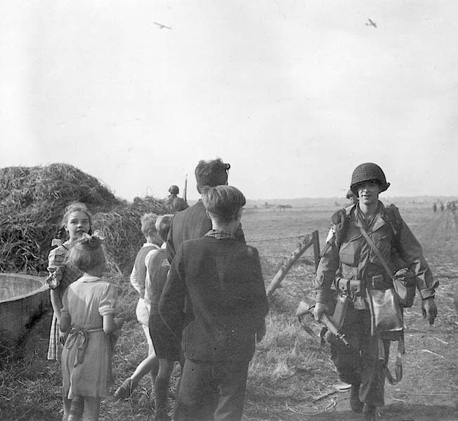 Anticipating that their liberation had begun, Dutch civilians greet an American 82nd Airborne Division paratrooper on the edge of a drop zone near the city of Nijmegen. The troopers of the 82nd assembled quickly and started off toward their assigned objectives but the operation would soon run into trouble.