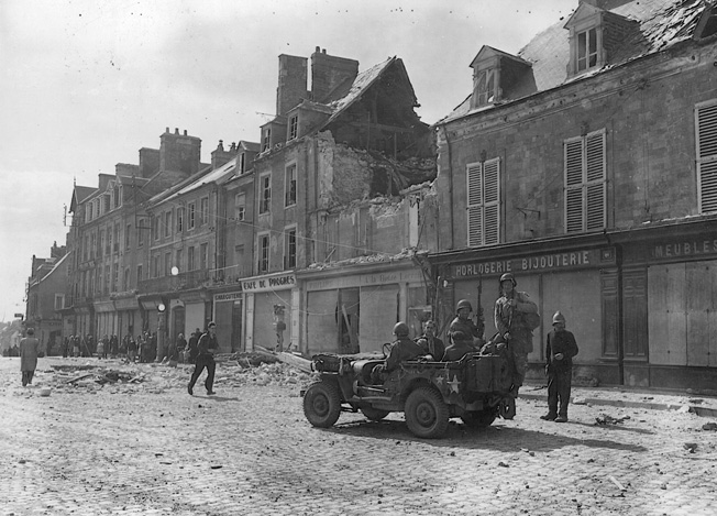 Eight days after the 101st parachuted into Normandy, American soldiers enter the bitterly contested French town of Carentan on June 14, 1944. Troopers of the 101st had taken the village during a tough fight with German air- borne troops and held it against a major counterattack.