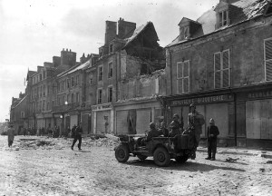 Several of them arriving aboard a jeep, troops of the 101st Airborne Division enter the important Norman town of Carentan on June 14, 1944.