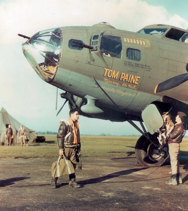 """A B-17 nicknamed """"Tom Paine"""" sits ready to begin a mission as its crew loads up for the coming fight. The bomber's base was near the birthplace of American patriot Thomas Paine in Thetford, England."""