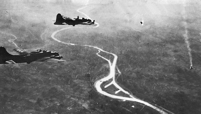 Pieces ofa  German Messerschmitt Me-110 twin-engine fighter spiral toward the ground as Eighth Air Force B-17s press on during a difficult raid against the manufacturing center of Schweinfurt, Germany,
