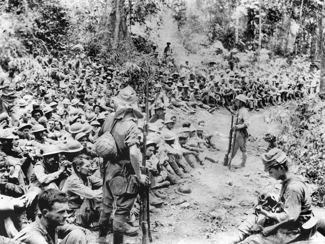 Japanese soldiers stand guard over American prisoners of war just prior to the start of the Bataan Death March during which thousands perished. Some 75,000 U.S. and Filipino soldiers were marched 65 miles to POW camps.