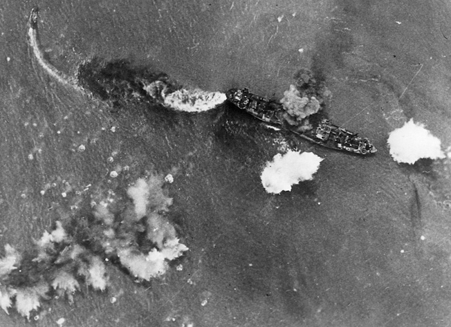 A stricken Japanese vessel billows smoke from a bomb hit amidships while a fire rages in the stern. Moments later, the transport settled to the bottom of the Bismarck sea. A smaller boat attempts to escape the debacle.