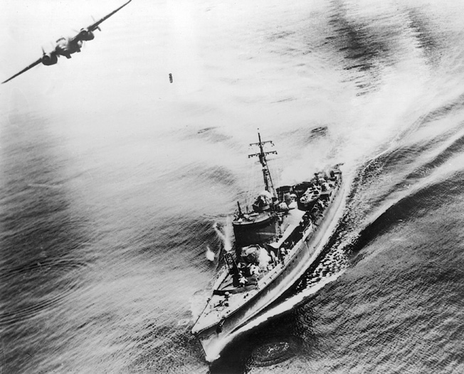 An American bomber banks away from a Japanese warship in the Bismarck Sea. Its bomb can be seen plummeting toward the pagoda-masted target below.