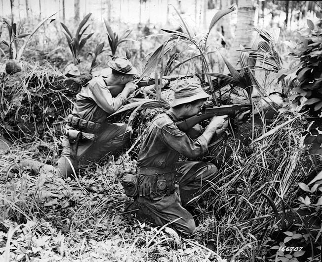 Armed with an M-1 Garand rifle and Thompson submachine gun, two men of the 32nd Division fire on Japanese positions near Buna. Although previously unschooled in jungle warfare, the 32nd learned quickly.