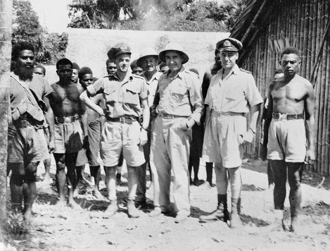 "Lt. Cmdr. W.J. ""Jack"" Read of the Royal Australian Navy Intelligence Division poses (hand on hip) with other personnel, including native scouts, at the Australian Intelligence Bureau Camp at Lunga, Guadalcanal, on March 27, 1945."