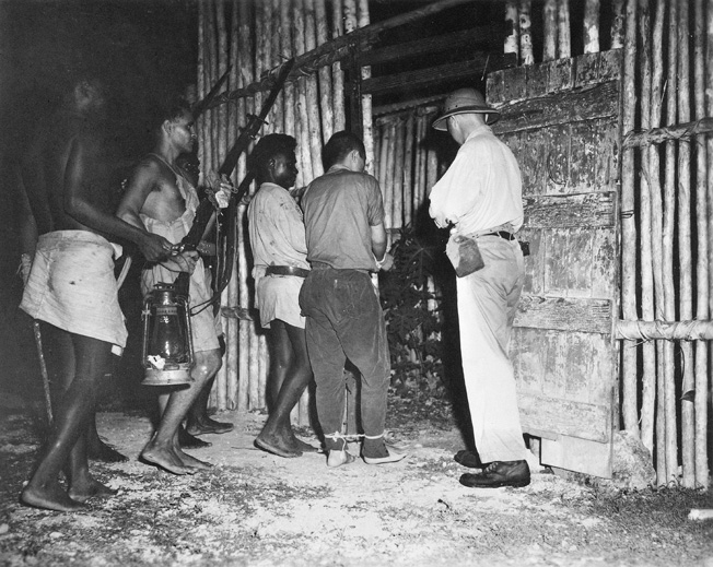An armed guard of native scouts trained and commanded by Captain D.G. Kennedy escorts a captured Japanese pilot into captivity at the Segi coast watchers' station on New Georgia in March 1943.