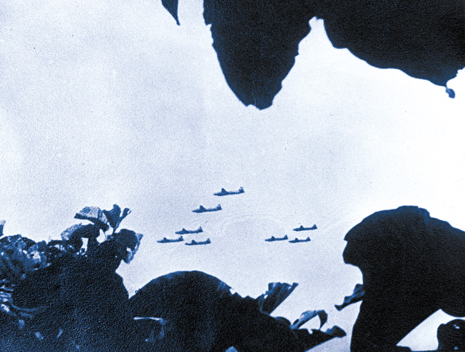 In a 1943 photo possibly taken by a coast watcher, a formation of Japanese Mitsubishi Betty bombers wings its way over New Guinea toward a distant target.