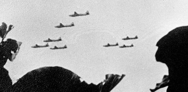 "A flight of Japanese Mitsubishi ""Betty"" bombers, possibly photographed by a coastwatcher in 1943, heads toward a distant target."