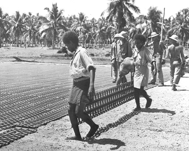 Native and American workers rush to complete the airfield the Japanese had begun to build at Lunga on Guadalcanal. Coast watchers had reported on Japanese progress in building the airfield, and from strategic points around the island warned of impending attacks on the area. The airfield was named Henderson Field.