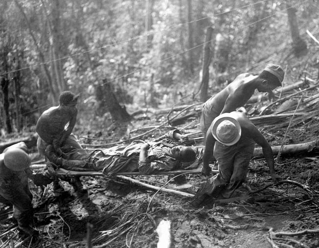 Shirtless 93rd Infantry Division soldiers carry a wounded buddy to an aid station on Hill 250 while under intense enemy fire, April 6, 1944.