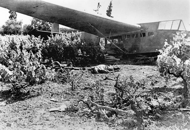 A crash-landed German glider lies near the main road bridge at Maleme Airfield on Crete. Control of the airfield was the key to the eventual German capture of the island, allowing supplies and reinforcements to land.