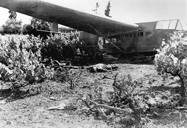Dead German assault troops lie sprawled alongside the wreckage of their glider in a wooded area on Crete.