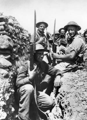A New Zealand unit armed with bolt-action Enfield rifles, sword bayonets, and a lone Thompson submachine gun wait for the enemy. Much of the British equipment and heavy weapons was left behind during the evacuation from Greece.