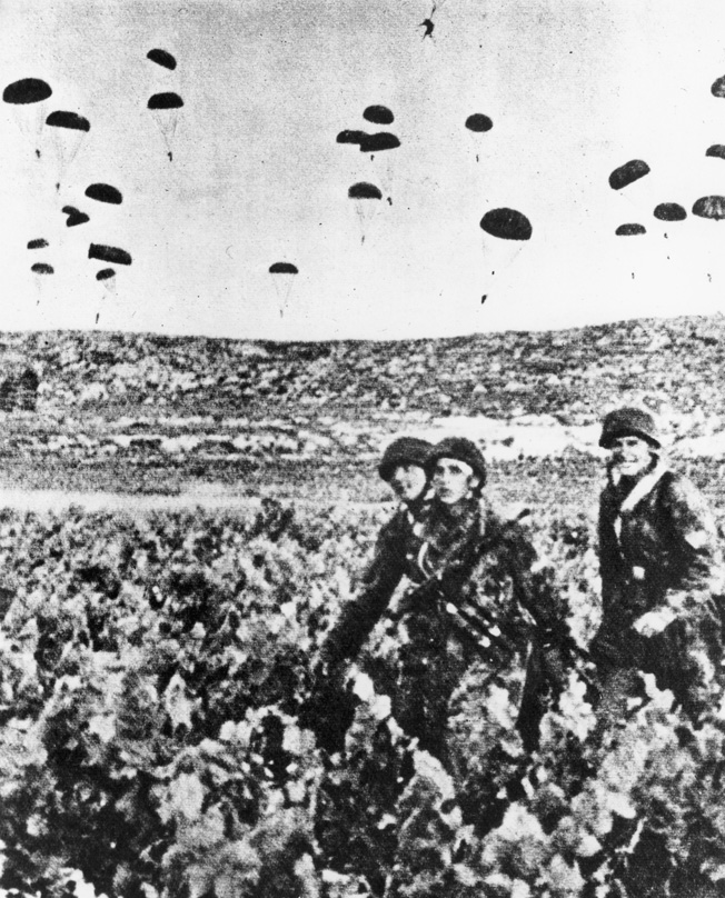 Glancing toward their photographer. three German paratroopers, wearing their distinctive rimless helmets, march off toward an assembly area while other fallschirmjager land in the field beyond.