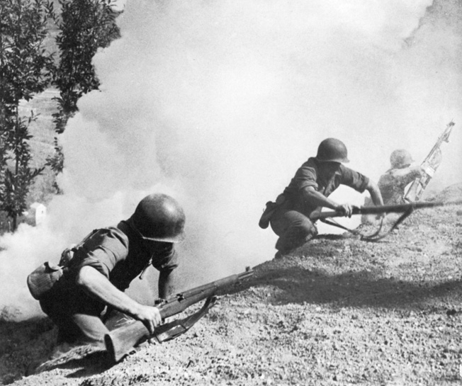 U.S. Rangers scramble up a hillside near Chiunzi Pass under a smoke screen.