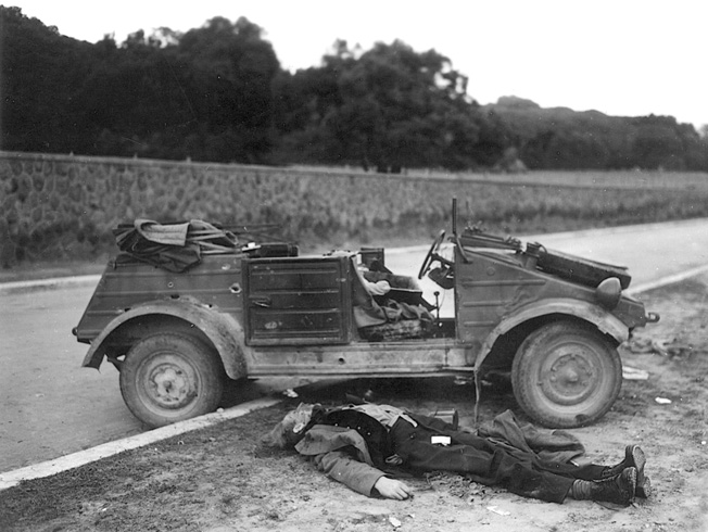 A dead German soldier sprawls next to his vehicle near the Anzio beachhead. Soldiers of the 1st Ranger Battalion caught the victim in an ambush.