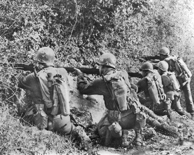Slugging their way through the mountains of Central Italy, U.S. Rangers lay down covering fire from a well-concealed position as other members of their squad execute the technique of fire and maneuver.