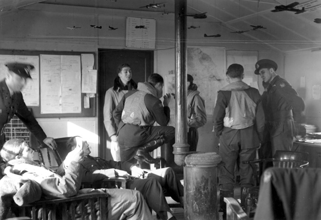 Eagle Squadron pilots engage in lively chatter and lounge around a dispersal hut as they await the word to take off on a training flight.
