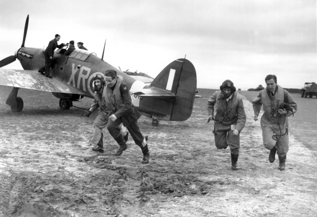As one aviator is strapped into the cockpit of his Hawker Hurricane fighter, other pilots of the Eagle Squadron dash to the aircraft as an alarm is sounded during the Battle of Britain.