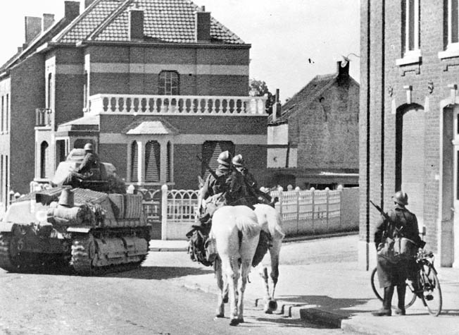 French soldiers on a tank, horses, and bicycle patrol a quiet French village. Soon, however, the Germans would arrive and life would never be the same again.