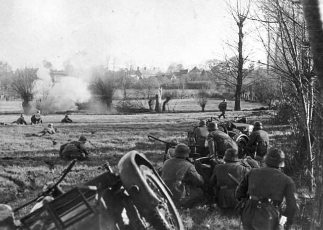 Temporarily halted by a machine-gun nest, members of a German motorcycle infantry platoon maneuver to silence the threat on the outskirts of a French village.