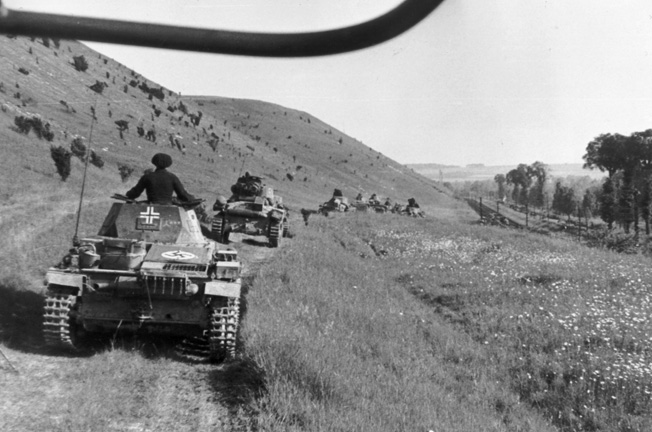 In a photo taken by legendary German commander Erwin Rommel or a member of his staff, panzers roll down a dusty road in pursuit of a beaten and demoralized enemy.