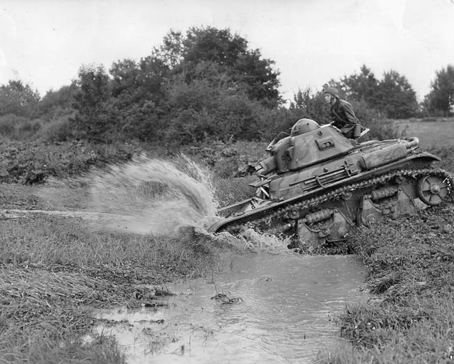 Attempting to ford a deep stream somewhere in Belgium, a French tank throws up a shower  of muddy water. Juin stopped the Germans at Gembloux but was forced to retreat when the Germans  managed to break through at Sedan and elsewhere.