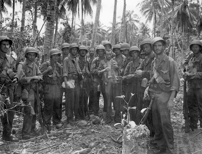 A U.S. Marine patrol pauses for a photograph after completing a reconnaissance mission on Guadalcanal. Their Japanese prisoner is a rare find indeed since enemy troops refused to be taken alive.