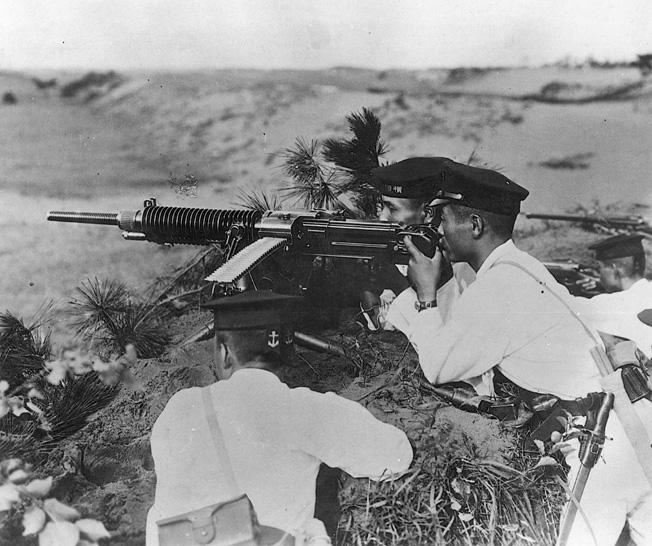 Clad in white uniforms and dress caps, Japanese soldiers fire a Nambu machine gun. Possibly a memento from his training days, the photo was found on the body of a dead Japanese soldier on Guadalcanal.