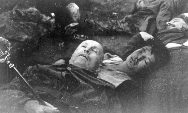 The corpses of Mussolini and his mistress Claretta Petacci, lie sprawled on the ground at the Villa Belmonte. They were later strung up in the city square of Milan.