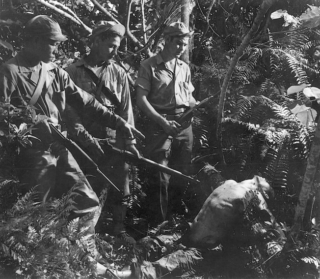 With their guns at the ready, members of a native military patrol stand over the body of a dead Japanese soldier on Guam in the Marianas.