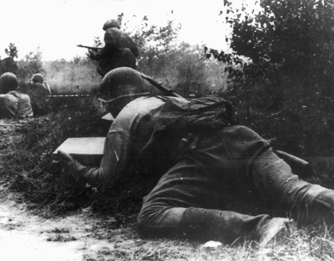 On August 12, 1942, a Red Army soldier crawls forward to deliver ammunition to comrades fighting to hold back a German counterattack on Soviet positions.