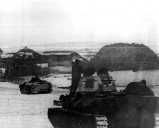 Moving toward the fighting at Kharkov during an offensive operation near the Don River, Red Army tanks advance through a temporarily quiet Russian village.