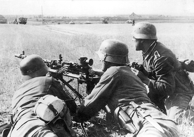 A German machine gun squad, one soldier equipped with a pair of field glasses, surveys the steppes for enemy targets. German forces inflicted heavy casualties on attacking Red Army units during their 1942 summer offensive.