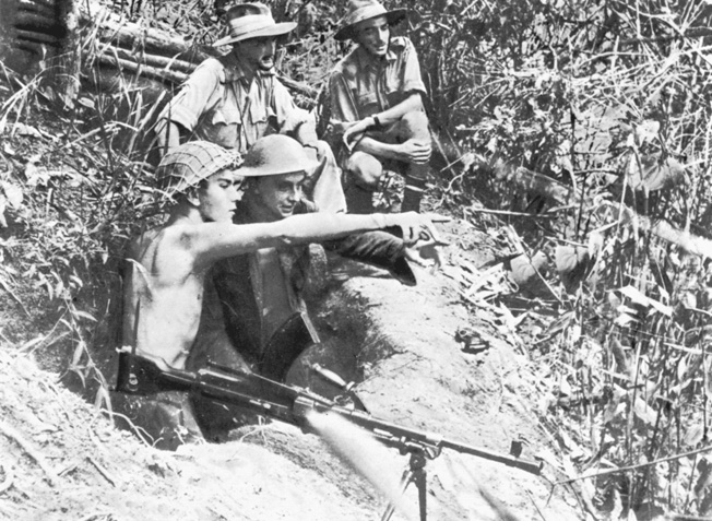 Positioned to command the high ground above an airfield in the Imphal Valley, a bren gun team of RAF personnel spots movement in the distant jungle.