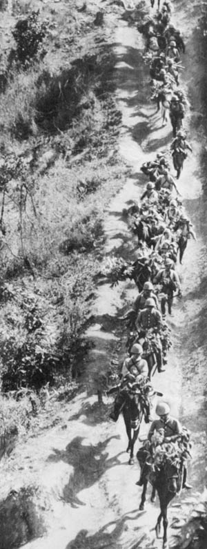 Japanese cavalrymen, some without mounts, traverse a dusty road during their advance toward koshima and Imphal in 1944. Losses among the horses were said to be greater than two-thirds.