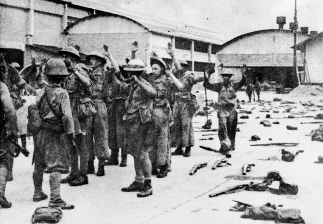 After their ignominious surrender at Singapore, British soldiers, their hands raised above their heads, are marched off into wretched captivity. Many of them did not survive, while others endured four years of harsh treatment at the hands of their Japanese captors.