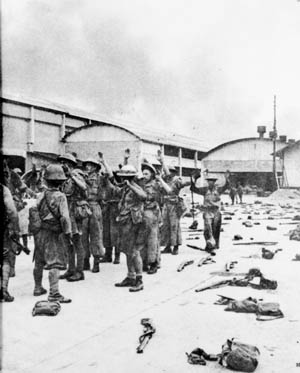 Their arms raised in surrender, British soldiers march toward years of captivity on February 2, 1942. The fall of Singapore was a disaster of the highest magnitude for the Allies.
