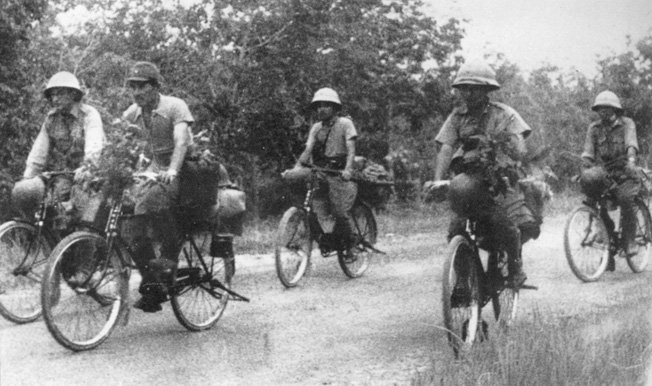 Riding bicycles, a Japanese unit rolls rapidly forward during the advance on Singapore. When the tires went flat, the soldiers continued to ride on the metal rims.