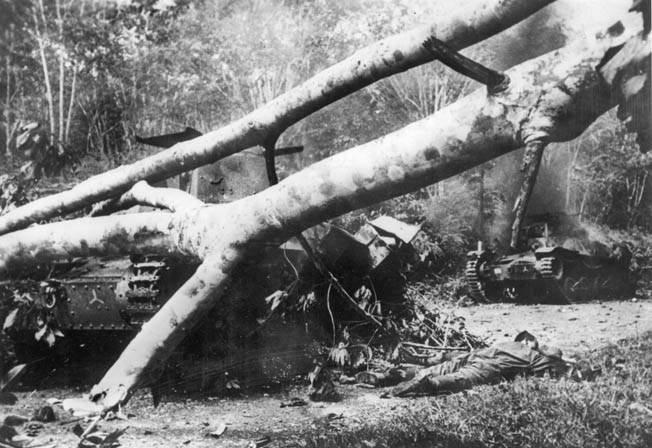 Two Japanese tanks smashed and set on fire by Australian antitank gunners lie among felled trees blockading a road in Malaya.