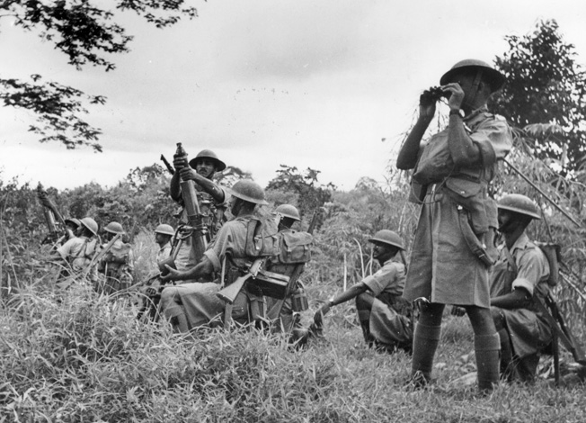 Standing their ground in the dense jungle of Malaya, Indian soldiers fire trench mortars from a tapioca patch at the oncoming Japanese.