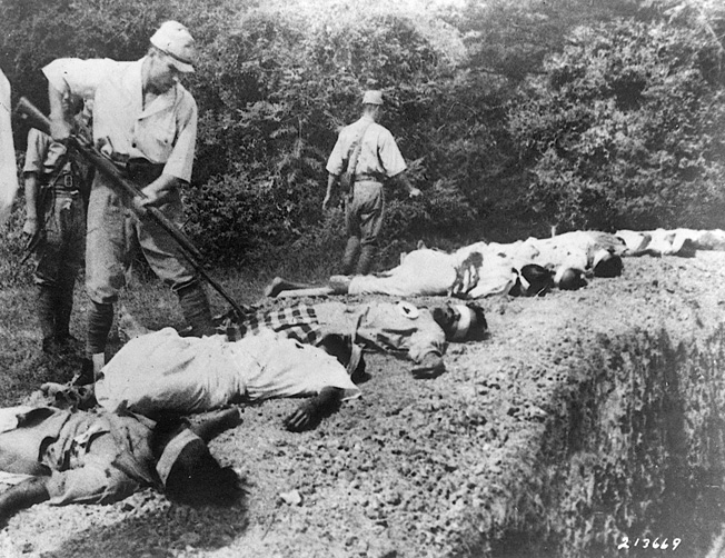 A Japanese soldier bayonets the body of a prisoner, one of several summarily executed by firing squad.