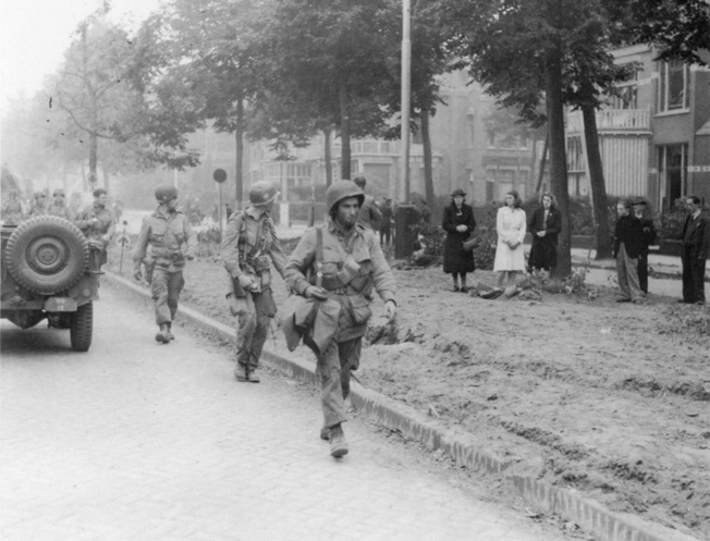Confused Dutch civilians turn out to watch American soldiers participating in the effort to relieve a battalion of British paratroopers that was isolated at Arnhem and clinging to a futile foothold at the east end of the bridge into the city.