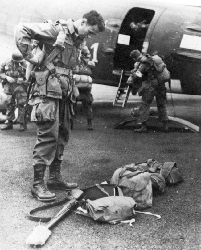 As he prepares to board a transport aircraft, Brig. Gen. James M. Gavin, commander of the U.S. 82nd Airborne Division, carries out a final check of his weapons and gear before heading toward his Market-Garden jump zone in Holland.