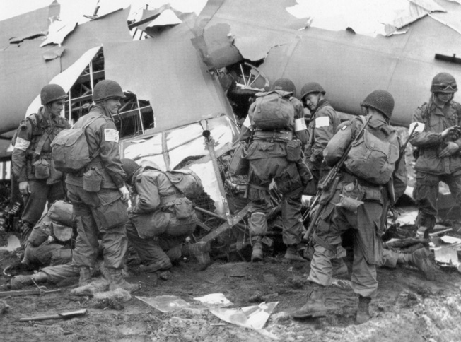 Gliderborne soldiers of the U.S. 82nd Airborne Division unload their wrecked aircraft after what amounted to a controlled crash in a Dutch field during the opening hours of Operation Market-Garden.